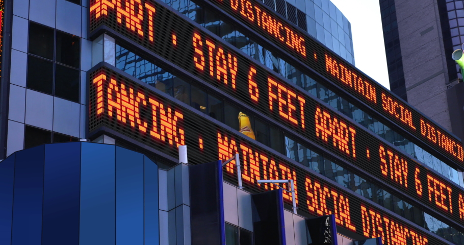 A fictional news ticker reminds pedestrians to keep 6 feet apart from each other. Social distancing was a common practice during the COVID-19 pandemic of 2020.	Custom text available upon request.