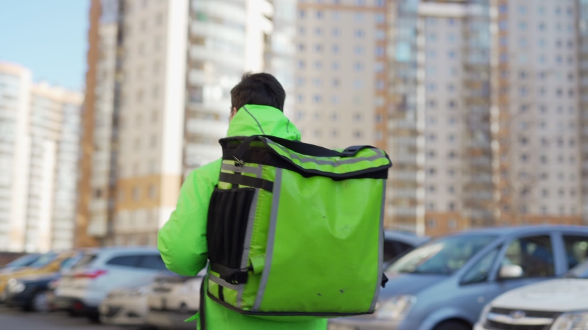 Panning shot of young male food courier wearing protective mask while walking down city street with insulated backpack delivering order Royalty-Free Stock Footage #1050411754