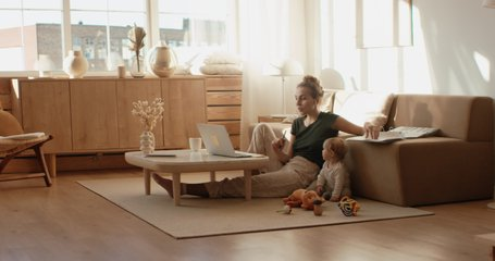 Caucasian mother working from home, having a work video call, daughter playing nearby. Stay home, quarantine remote work. Shot on RED Dragon