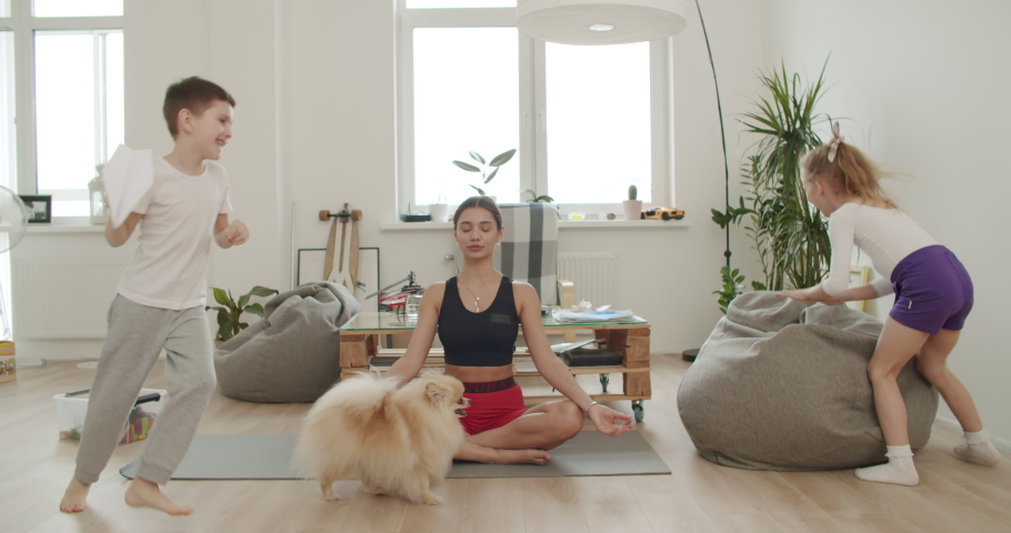 Mother meditating with daughter while active energetic child son playing, calm young mom doing yoga exercise at home for stress relief relaxing with naughty little kid. 4k video footage slow motion | Shutterstock HD Video #1050423673