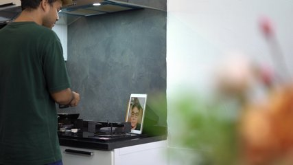 Social distance and work from home  concept, Asian man video conferencing with friend on his tablet and cooking in the kitchen room during lockdown situation.