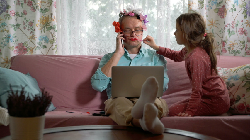 Home quarantine self-isolation. A middle-aged man working remotely from home. His little daughter getting in the way all the time. She tieing bows on his head, painting his lips and putting on makeup