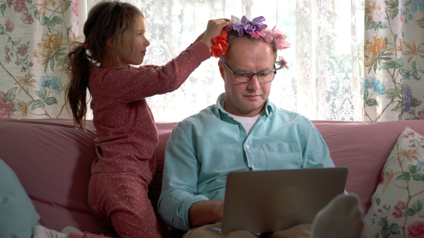 Home quarantine self-isolation. A middle-aged man working remotely from home. His little daughter getting in the way all the time and tieing bows on his head.