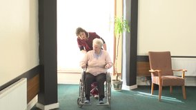 Carer pushes an Elderly Senior woman in her Wheelchair in a Care Home. Social Care. Stock Video Clip Footage