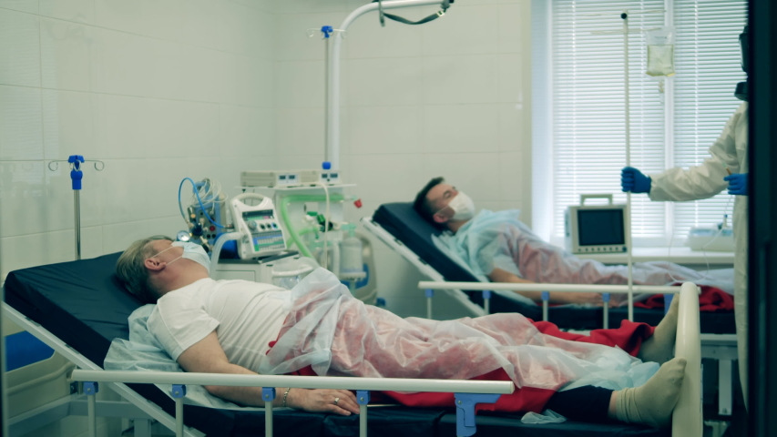 A physician in protective suit gives a patient an IV during pandemic. Coronavirus, covid-19 patient in intensive care unit at a hospital. Royalty-Free Stock Footage #1050442831