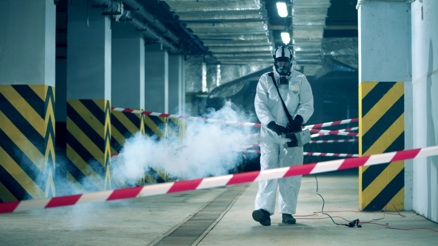 A sanitation worker disinfects room. Coronavirus prevention, covid-19 protective disinfection. Royalty-Free Stock Footage #1050442990
