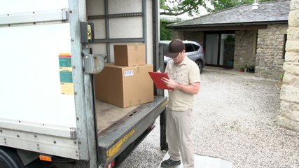 Courier / Delivery man writes on clipboard with parcel in the back of a  shipping / freight truck. Logistics. At home / House. Stock Video Clip Footage