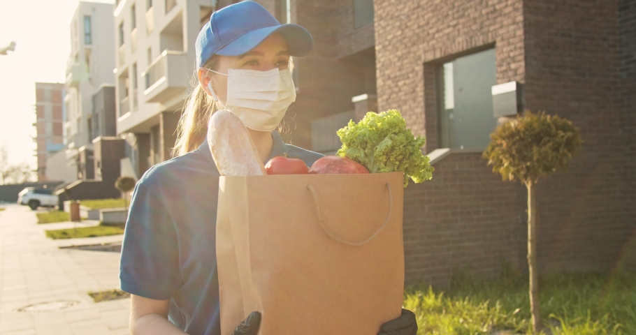 Caucasian young pretty woman, delivery worker in bluetooth headphones, cap and medical mask walking the street and carrying packet with fresh food. Female beautiful courier going to deliver grocery.