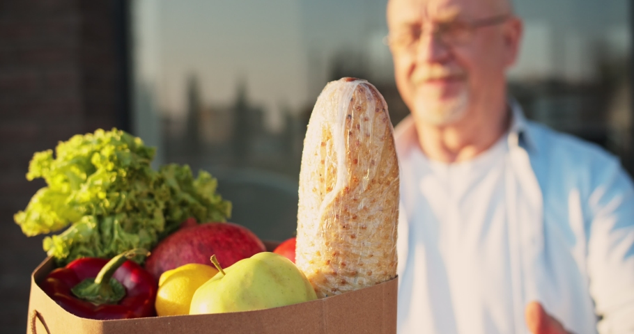 Close up of baguette and fresh vegetables in packet. Courier bringing food to old Caucasian man and handing outdoor. Deliveryman bringing grocery to male pensioner. Royalty-Free Stock Footage #1050465964