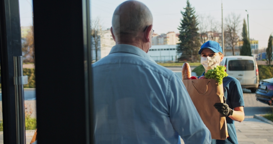 Rear senior man coming out from building and meeting young Caucasian female courier from supermarket. Woman in medical mask and gloves handing packet with food to male. Coronavirus isolation concept Royalty-Free Stock Footage #1050466042