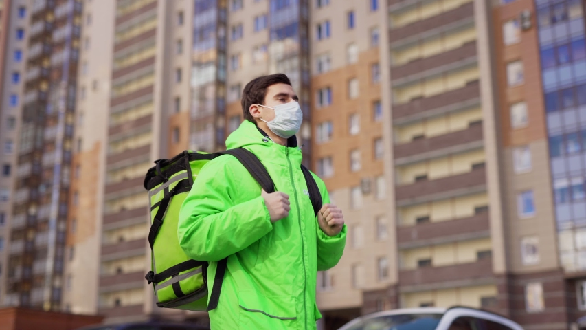 Tracking medium shot of delivery guy wearing medical mask and green uniform while walking along buildings down city street with insulated bag  | Shutterstock HD Video #1050466876