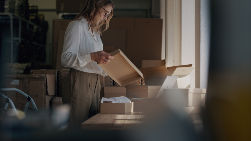 Woman checking a laptop for new order and packing the product for delivering to the customer. Online business owner working at the office, preparing the order  Royalty-Free Stock Footage #1050470638