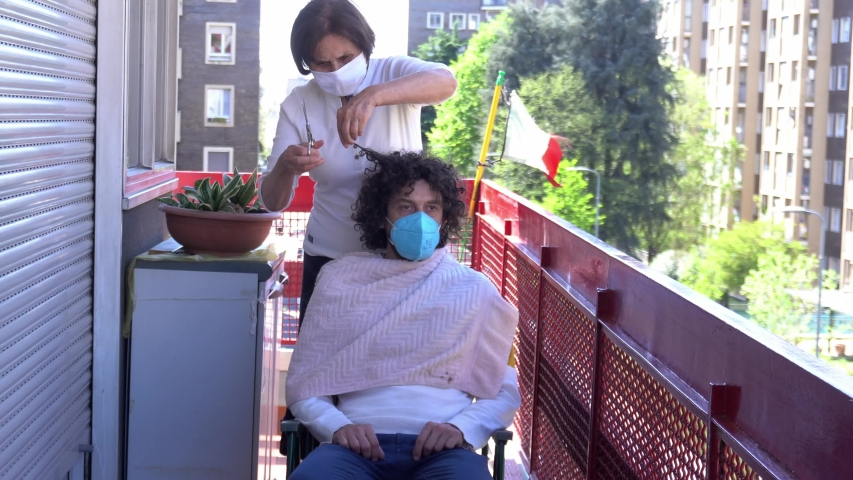 Europe, Italy, Milan - Pandemic emergency n-cov19 Coronavirus - Domestic life in quarantine of 70 year Italian old lady  with  mask CUT  HAIR ON THE BALCONY OF  HOME TO SON/ GRANDDAUGHTER Royalty-Free Stock Footage #1050470923