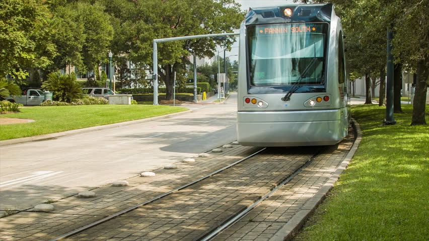 HOUSTON, TX - 2015: Metro Light Rail Public Transportation Passing Hermann Park in Houston Tx on a Sunny Texas Day with  Traffic and City in Background during the Summer with Green Grass | Shutterstock HD Video #10504814