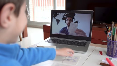 Child studying homework math during his online lesson at home, social distance during quarantine. Self-isolation and online education concept caused by coronavirus pandemia
