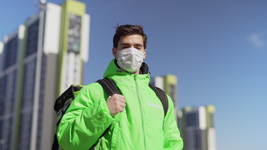 Medium shot portrait of young male food courier in medical mask and green uniform looking at camera while posing with insulated bag standing in city street | Shutterstock HD Video #1050495718
