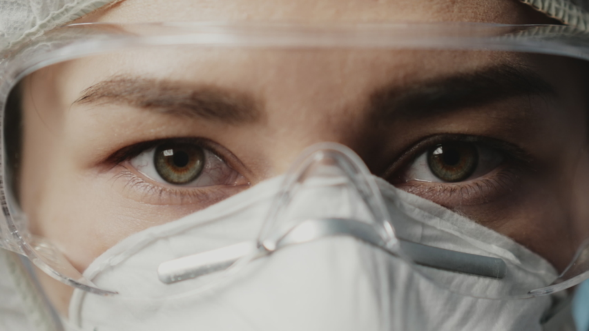 Portrait of confident doctor woman face, close-up. eyes with safety glasses and protective mask. Research Laboratory Officer. 2019 Novel Coronavirus (2019-nCoV), COVID-19, pandemic, isolation concept. | Shutterstock HD Video #1050499081