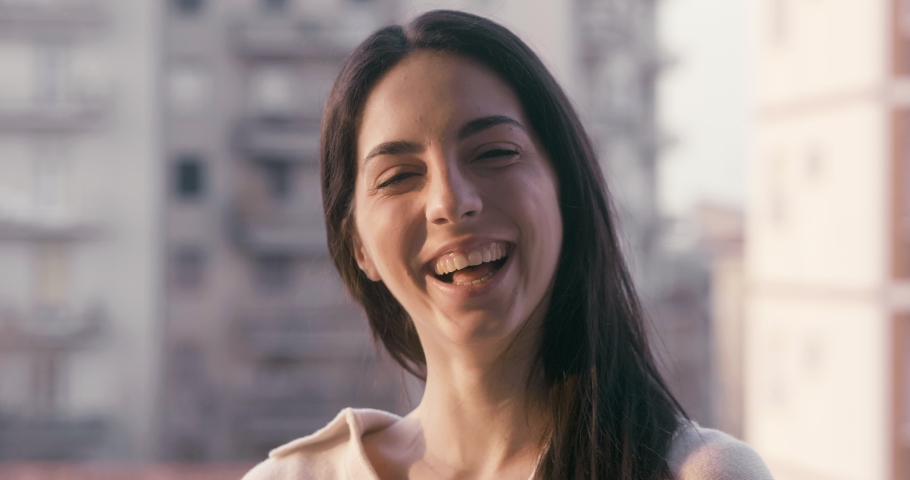 Authentic shot of an young carefree woman is looking and laughing in camera on a background of apartment buildings. Concept: freedom, life, dreams,hope, new beginning,environment,quarantine, covid_19 | Shutterstock HD Video #1050502654
