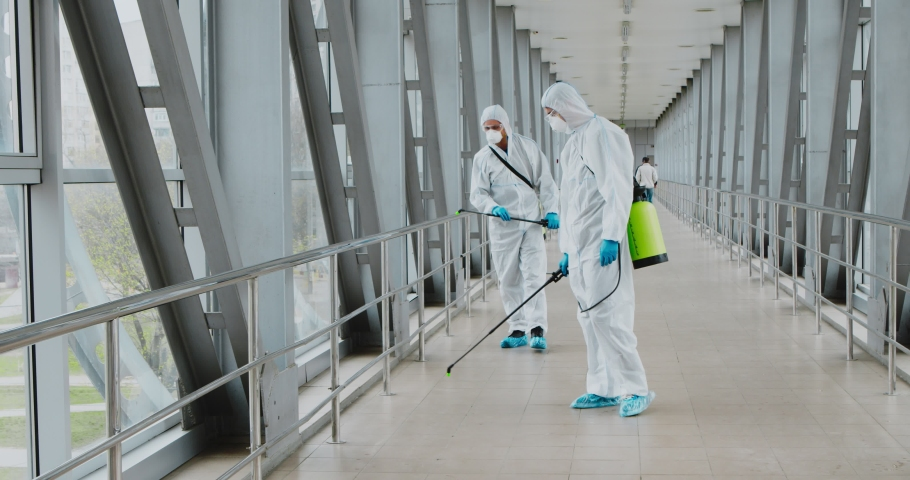 Public places disinfection. Specialists in hazmats cleaning handrails with chemicals Royalty-Free Stock Footage #1050507190