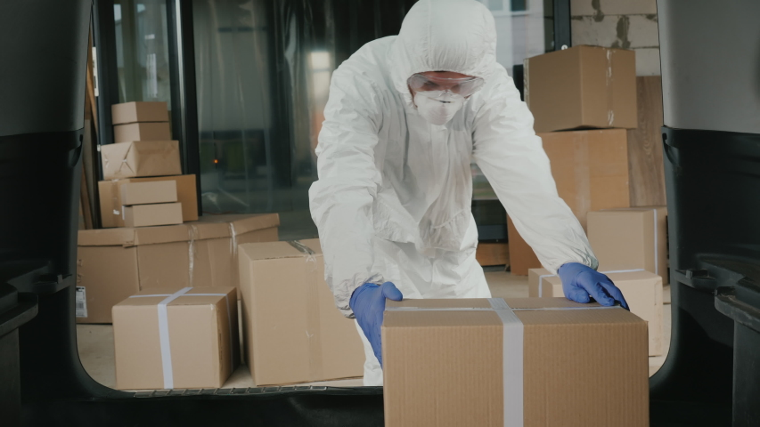 Worker in protective clothing loads boxes of medicines into the trunk of the car | Shutterstock HD Video #1050519952