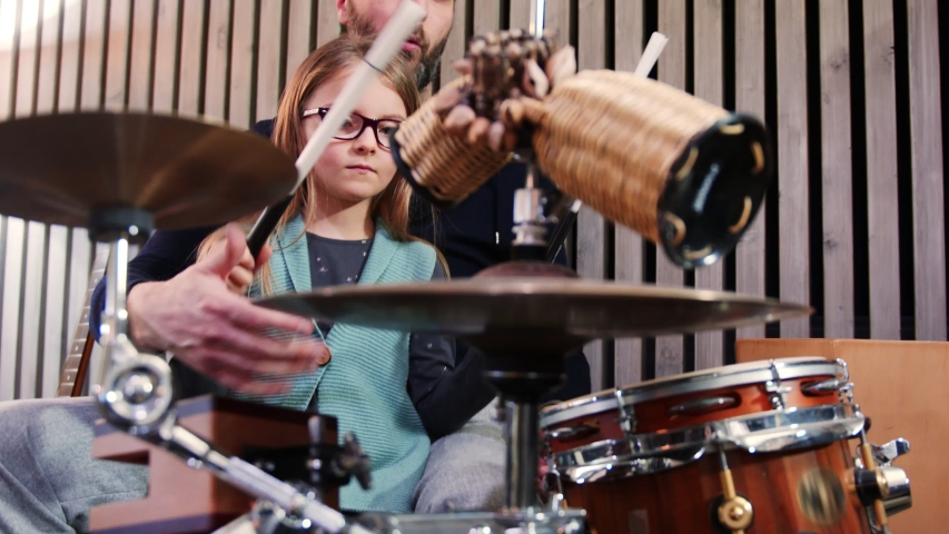 Father and daughter play percussion together.Little girl learning drums with her dad at home.Front view.Percussion class at home | Shutterstock HD Video #1050522466