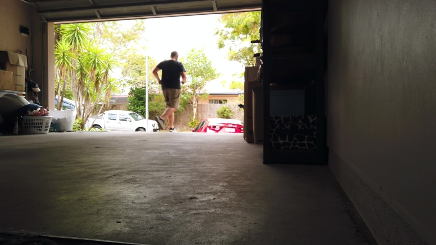 Man leaving the house through the garage, looking for something