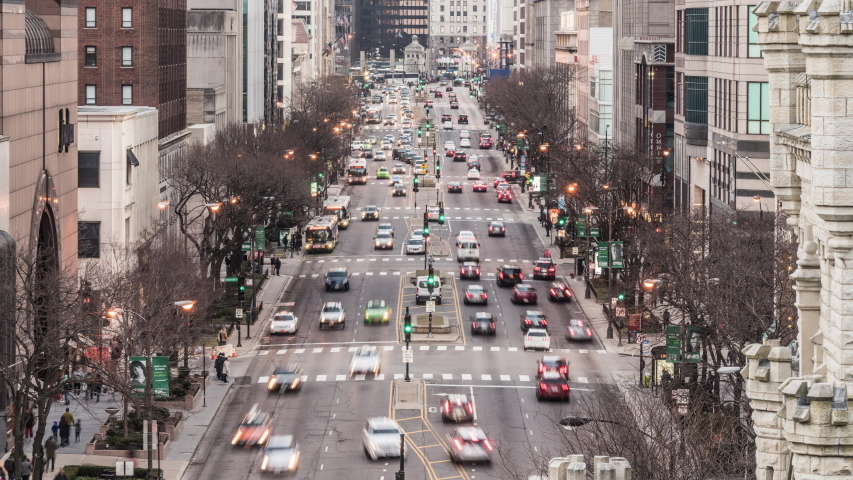 Chicago, United States - Mar 18, 2019: Time-lapse of car traffic transportation on road and people walk on Magnificent Mile shopping street district. Commuter transport or American lifestyle concept