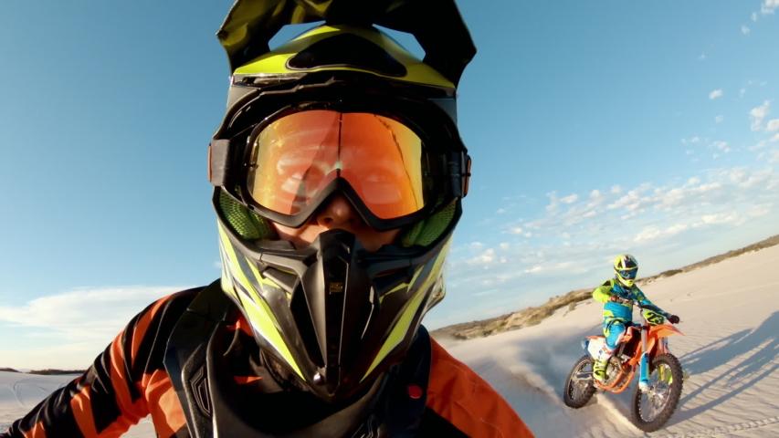 Shot from helmet mounted action camera of professional dirt bikers practising in desert. Motorcylists doing off roading on sand dunes.  | Shutterstock HD Video #1050529093