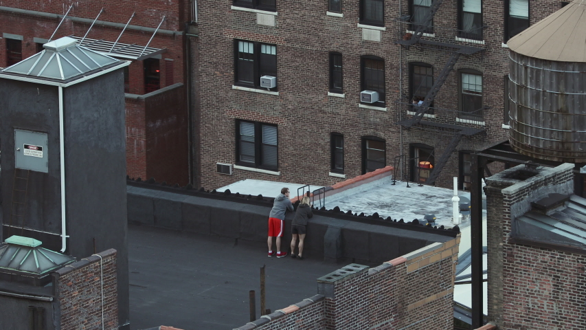 NEW YORK, NY, USA - 07 APRIL 2020: Upper West Side New York Coronavirus shelter in place Clap because we care couple on rooftop clapping and cheering for healthcare workers covid-19 virus outbreak