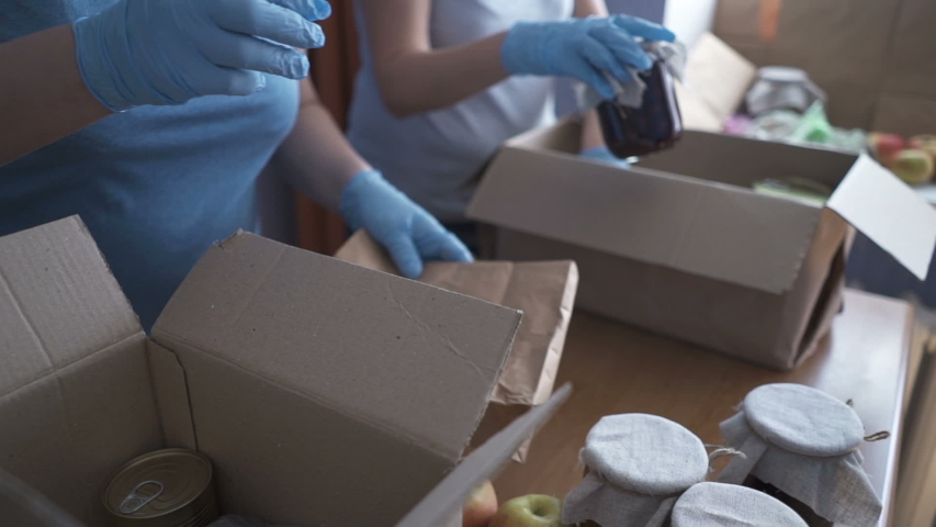 Volunteers in protective suits pack products. Food delivery services during coronavirus pandemic for working from home and social distancing. Shopping online. | Shutterstock HD Video #1050537601