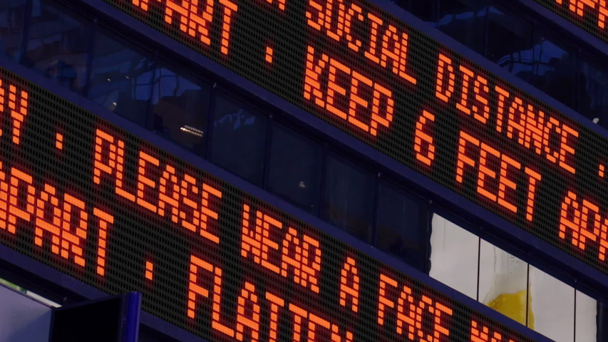 Closeup view of a Times Square ticker reminding pedestrians to keep 6 feet apart from each other. Social distancing was a common practice to slow the spread of COVID-19 during the pandemic of 2020.   | Shutterstock HD Video #1050539182