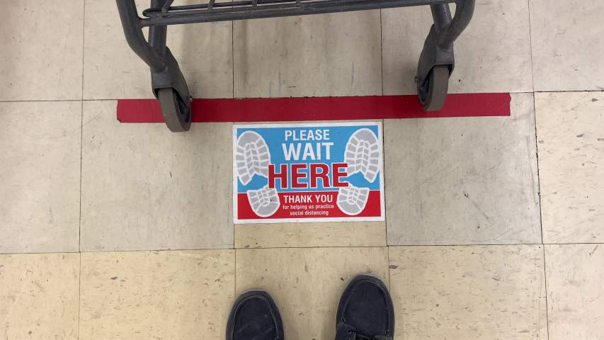 A view of a social distance sticker on the floor at the checkout line in a department store. Social distancing was a common practice to reduce the spread of COVID-19 during the pandemic of 2020.  | Shutterstock HD Video #1050539218