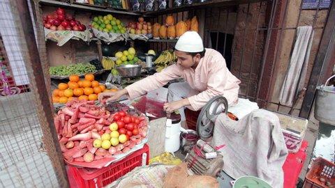 AGRA, UTTAR PRADESH, INDIA - FEBUARY 24, 2015: Muslim man making fresh carrot juice in his shop on the Taj Ganj Street