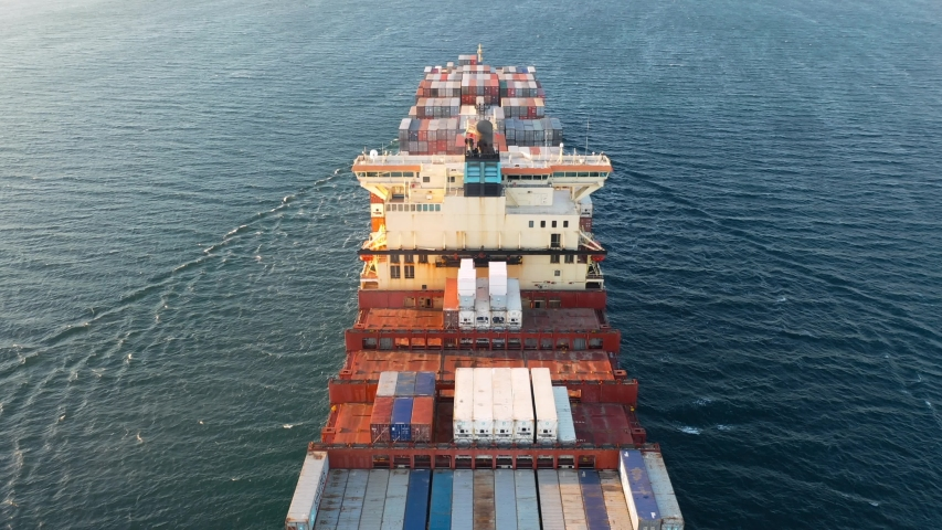 Flying over a cargo ship loaded with container stacks, heading towards the open sea. Funnel exhaust gases from diesel engine of a container ship. Marine air pollution concept    Shutterstock HD Video #1050545875