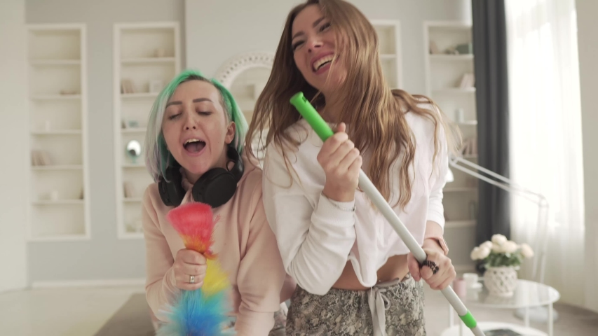 Two cheerful girls sing while cleaning the house. Friends have fun at home. | Shutterstock HD Video #1050551794