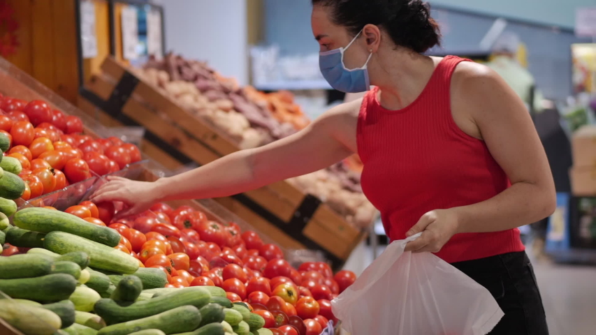 Young woman in a mask from a coronavirus epidemic is standing in the grocery department of a supermarket. She is buying quickly picking up food, where people are buying up food in a panic.   Shutterstock HD Video #1050558805