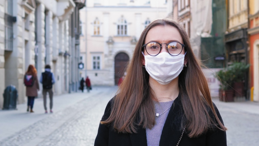 Young woman stands in medical mask and glasses in city. Female portrait is in white mask looking at camera. Coronavirus quarantine time. Health care and medical concept close up. Shot in 4k UHD 2160p | Shutterstock HD Video #1050562426