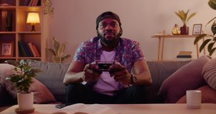 Front view of excited african guy playing video game and using joystick . Handsome young man wearing cap enjoying free time alone while sitting on couch in living room.
