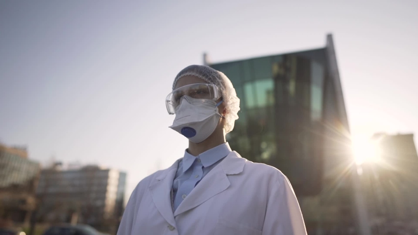 Equipped doctor waiting for patients in front of isolation ward medical facility.Coronavirus COVID-19 physician in PPE. City infectologist. Medical worker on the frontline | Shutterstock HD Video #1050590743