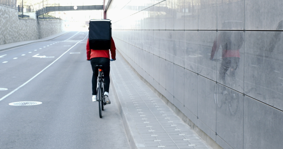 TRACKING Courier wearing medical mask and gloves riding a bicycle to deliver food order to customers during virus outbreak. Coronavirus, COVID-19, safe delivery | Shutterstock HD Video #1050598972