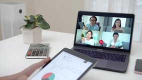 Zoom out of business woman talking about sale report in video conference. Asian team using laptop and tablet online meeting in video call.Working from home, Working remotely and Self isolation.