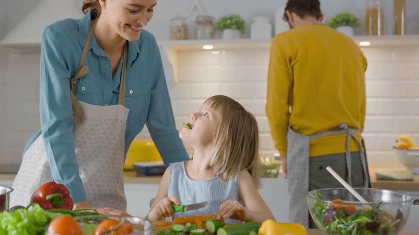 In the Kitchen: Mother and Cute Little Daughter Cooking Together Healthy Dinner. Mom Teaches Little Girl Healthy Habits and how to Cut Vegetables for the Salad. Cute Child Helping Her Caring Parents Royalty-Free Stock Footage #1050603106