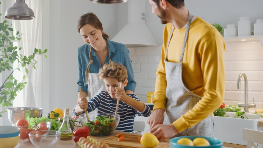 In the Kitchen: Mother, Father and Cute Little Boy Cooking Together Healthy Dinner. Parents Teach Little Son Healthy Habits and how to Mix Vegetables in the Salad Bowl. Cute Child Helping His Parents