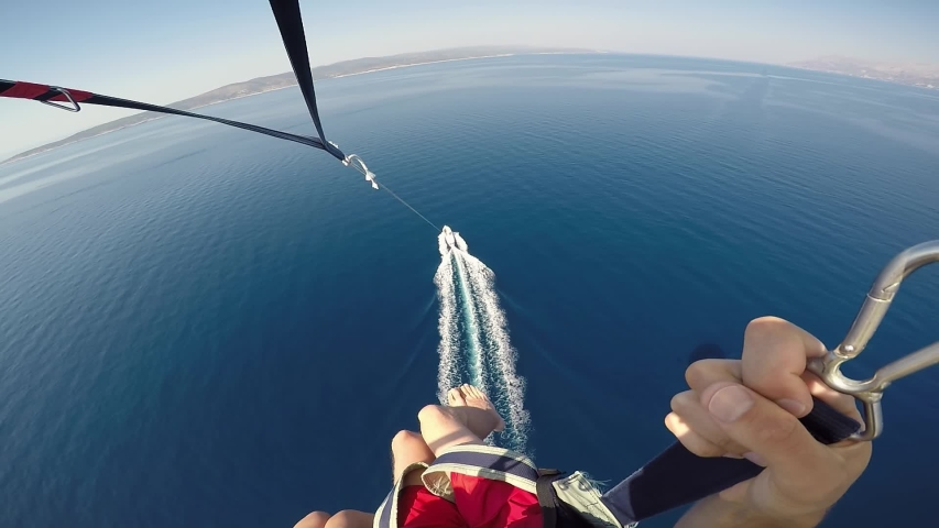 Amazing parasailing over Adriatic sea Croatia. First person view of parachute slings and bar with carabiners high above crystal blue water and motorboat | Shutterstock HD Video #1050606418