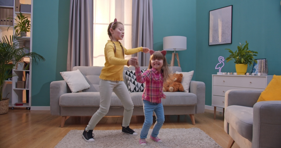 Caucasian teen small pretty girls in funny ears listening to music and dancing in cozy living room. Cheerful cute kids dance and having fun together at home. Little sisters moving with favorite song. | Shutterstock HD Video #1050615022