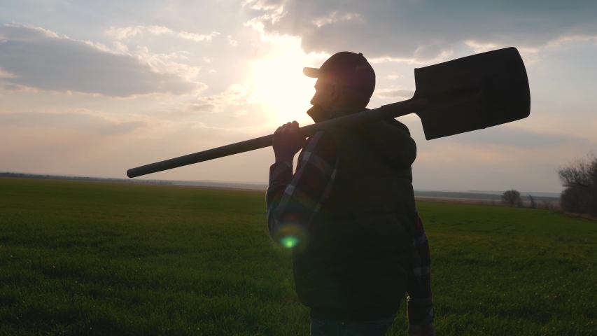 An agronomist man walks through a black plowed field at sunset. Farmer with a shovel in his hands. | Shutterstock HD Video #1050618259