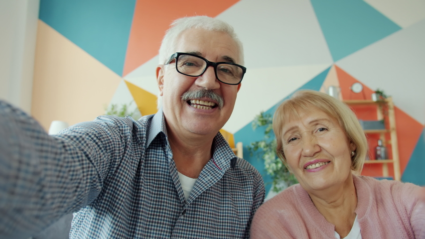 Portrait of lovely old couple enjoying online video call showing thumbs-up talking laughing looking at camera. Communication and technology concept. Royalty-Free Stock Footage #1050618472