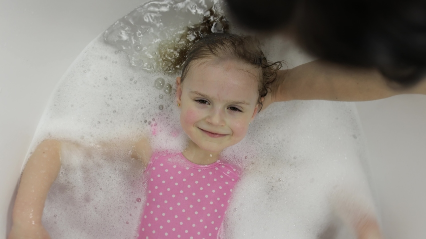 Attractive four years old girl takes a bath with bath foam in pink swimwear. Mother washes her daughter's hair. Bath foam on head. Hygiene for cute blonde child. Little blonde child girl in bathroom   Shutterstock HD Video #1050628246