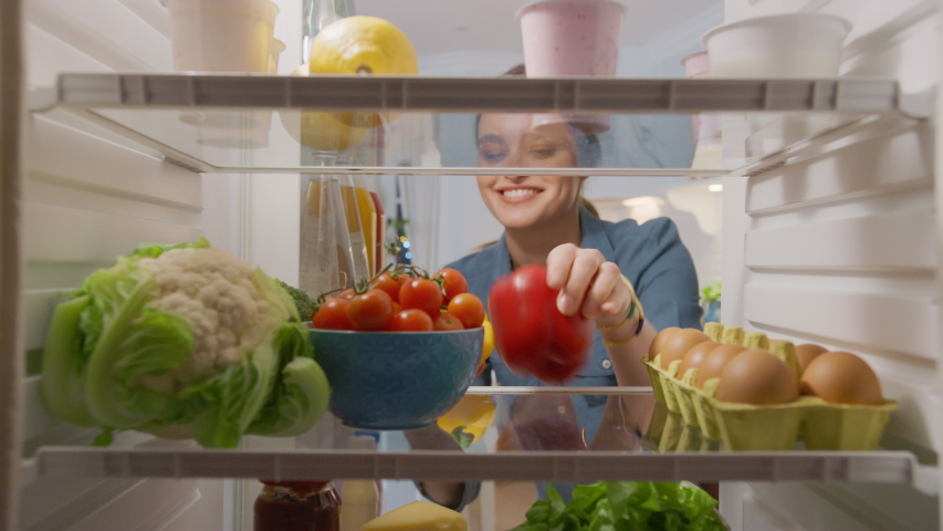 Beautiful Young Woman Opens Fridge Door, Looks inside Takes out Vegetables. Woman Preparing Healthy Meal Using Groceries. Point of View POV from Inside of the Kitchen Refrigerator full of Healthy Food Royalty-Free Stock Footage #1050644704