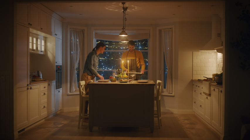 Happy Couple Cooking and Having Dinner Together. They Prepare Food, Serve Table. Lovely Boyfriend and Girlfriend Have Romantic Evening with Wine, Festive Table in Stylish Cozy Kitchen Interior Royalty-Free Stock Footage #1050644707